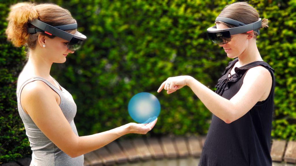 Zwei Frauen mit Hololens, eine hält eine Hologrammkugel auf der Handfläche