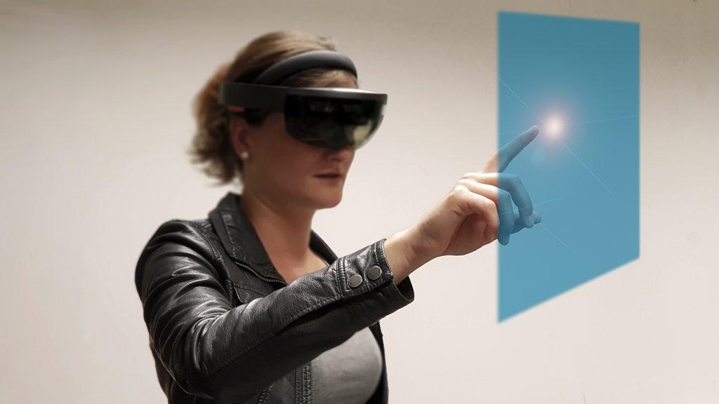 Frau mit Hololens zeigt auf Hologramm